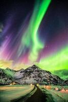 aurores boréales aurores boréales explosion au-dessus des montagnes et des routes rurales photo