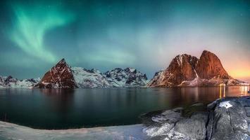 panorama des aurores boréales sur la montagne dans le village de pêcheurs de hamnoy en hiver photo