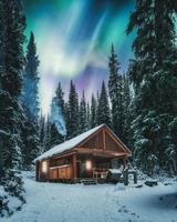 aurores boréales sur chalet en bois avec de la fumée sur la neige dans la forêt de pins au parc national yoho photo