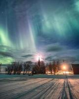 aurores boréales au-dessus de l'église chrétienne avec la lune photo