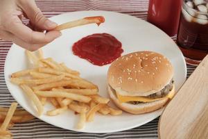 gros plan, mise au point sélective. la main de l'homme mangeait du ketchup frit sur une assiette blanche sur une nappe rouge avec des hamburgers et du cola. manger de la malbouffe ou de la restauration rapide pour le déjeuner est malsain. photo