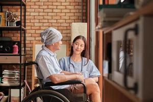 les patients âgés atteints de cancer en fauteuil roulant reçoivent un traitement de rééducation dans une maison privée, des traitements médicaux de femme médecin asiatique en parlant pour guérir la solitude et les encourager avec un sourire photo
