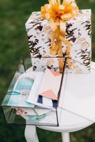 boîte en verre avec des cadeaux de mariage dans des enveloppes photo