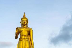 une statue de bouddha doré avec ciel au sommet de la montagne au parc public de la municipalité de hat yai, province de songkhla, thaïlande photo