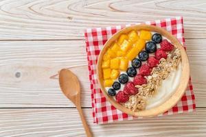 bol de yaourt fait maison avec framboise, myrtille, mangue et granola - style alimentaire sain photo