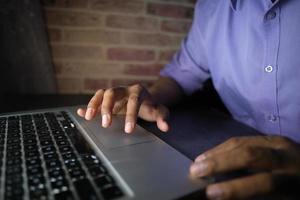jeune homme travaillant sur un ordinateur portable volant des données personnelles photo