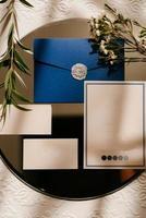 invitation de mariage dans une enveloppe grise sur une table avec des brins verts photo