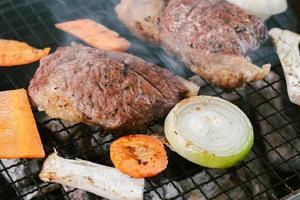 griller le bœuf sur le gril à charbon pour cuire les steaks photo
