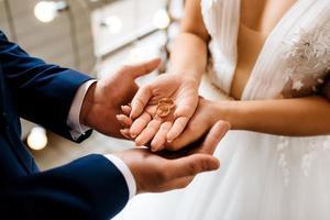 le marié met la mariée sur l'anneau de mariage photo