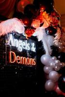 une zone photo sur le thème des anges et des démons en noir avec des boules blanches et noires