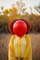 femme dans un imperméable jaune tenant un ballon rouge sur fond de forêt. photo