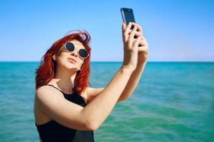 femme rousse prend selfie sur l'appareil photo du smartphone