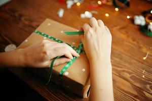 les mains des femmes attachant le ruban sur le cadeau de Noël. photo