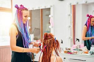 coiffeuse femme tisse des dreadlocks au gingembre pour fille. photo