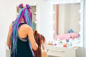 coiffeuse aux tresses afro colorées tisse des dreadlocks au gingembre. photo