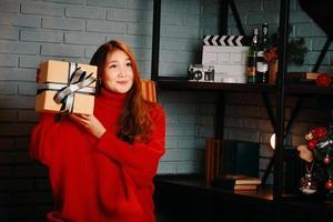 fille asiatique avec un cadeau dans ses mains. photo
