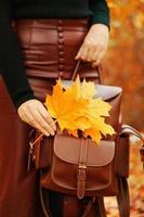 femme avec un sac à dos et feuillage. photo