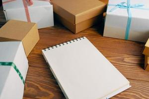 table en bois avec coffrets cadeaux et bloc-notes vierge. photo