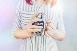 une femme tient un bocal en verre de pièces de monnaie pour son rêve. photo