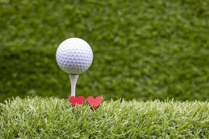 la balle de golf est sur le tee et deux coeurs rouges sur l'herbe verte avec amour photo