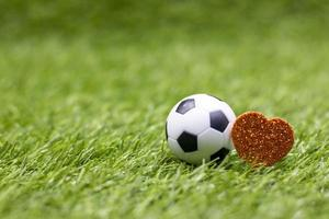 ballon de football est sur l'herbe verte avec amour coeur rouge photo