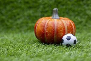ballon de football avec citrouille sont sur l'herbe verte photo
