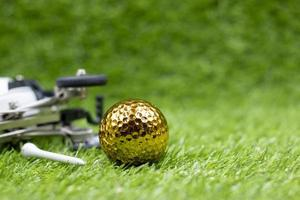 la balle de golf dorée est sur l'herbe verte photo