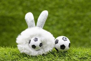 ballon de football avec décoration de vacances de pâques sur fond d'herbe verte photo