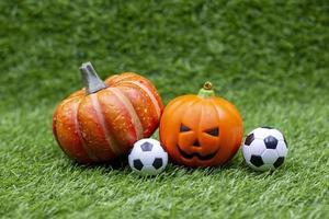 ballon de football pour le jour d'halloween avec citrouille sur l'herbe verte photo