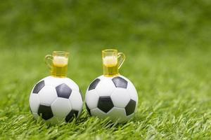 ballon de football avec des verres de bière sont sur l'herbe verte photo