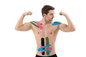 athlète professionnel masculin avec bande de kinésiologie sur le ventre et l'épaule. sport et rééducation, cure de kinésithérapie photo