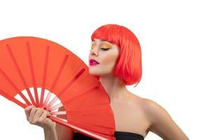Belle fille portant une perruque rouge tenant un ventilateur rouge isolé sur fond blanc photo