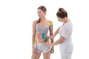 concept de perte de poids. bande de kinésiologie. thérapeute appliquant une bande de kinésiologie sur le ventre du patient. procédure anti-cellulite pour le ventre mince. perte de graisse, élimination de la cellulite, physiothérapie sportive, concept de récupération. photo