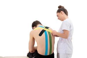 Jeune femme physiothérapeute appliquant un ruban physio spécial sur le dos de l'homme photo