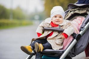 bébé assis dans une poussette, les yeux ouverts, en chapeau et veste, hiver ou automne. portrait. photo