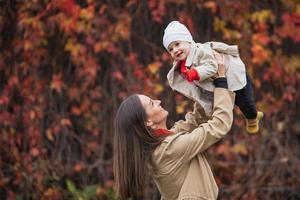 baie avec maman dans le parc en automne. maman et fille à l'automne. maman tient le bébé dans ses bras. mère avec sa petite fille dans le parc en automne lors d'une promenade. photo