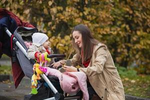 la mère met de petites chaussures à son bébé dans le parc d'automne photo