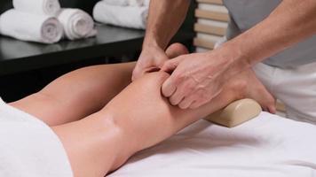 gros plan extrême de l'ostéopathe appliquant une pression avec le pouce sur le muscle du mollet féminin. photo
