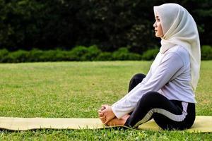 jeune femme musulmane faisant des étirements musculaires avant de faire des mouvements de yoga photo