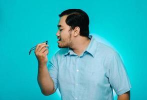 Jeune homme soufflant des verres à la main sur fond bleu photo