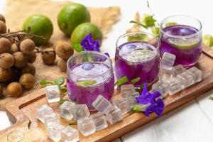 verre de jus de citron, fleurs de pois et longane sur table en bois blanc photo