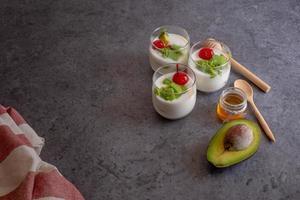verre de cerise et d'avocat en tranches de yaourt sur fond de bois photo