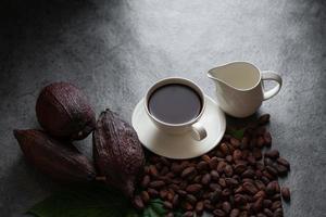 chocolat chaud et cabosse de cacao coupés exposant les graines de cacao sur une table sombre, vue de dessus avec espace de copie photo