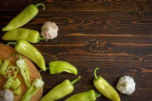 piments verts et chili tranchés avec de l'ail sur fond de bois photo