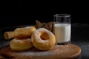beignets avec du sucre sur une plaque en bois sur un fond de table sombre. photo