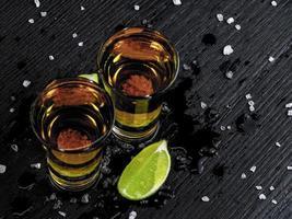 deux shots de tequila gold avec du citron vert juteux et du sel de mer photo