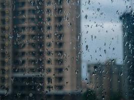 gouttes de pluie sur la fenêtre. fenêtre humide lumières de la ville gouttes de pluie photo