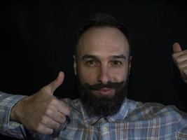 homme avec barbe et moustache faisant comme sur fond noir photo