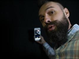un homme élégant avec une barbe et une moustache regarde dans le téléphone et fait un selfie sur fond noir photo