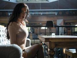 jolie fille aux cheveux bouclés et aux longues jambes dans une jupe courte est assise sur le canapé à la table photo